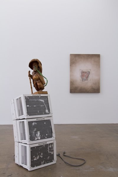 Foreground: Ouroboros, 2015, air conditioning units, wooden figure, rubber snake. Background: Untitled, 2014, photograph, knitting template on canvas